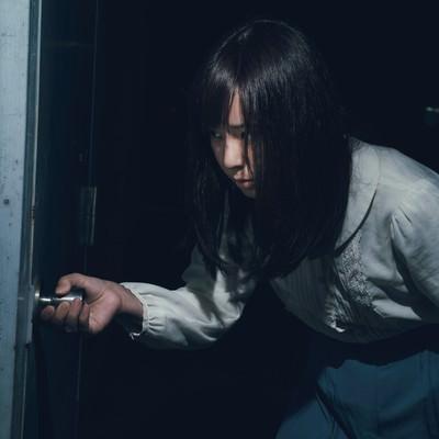 「恐る恐る扉を開ける女性」の写真素材