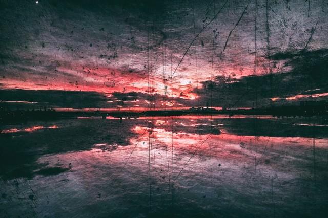 夕焼け赤く反射する水面(ノイズ)の写真