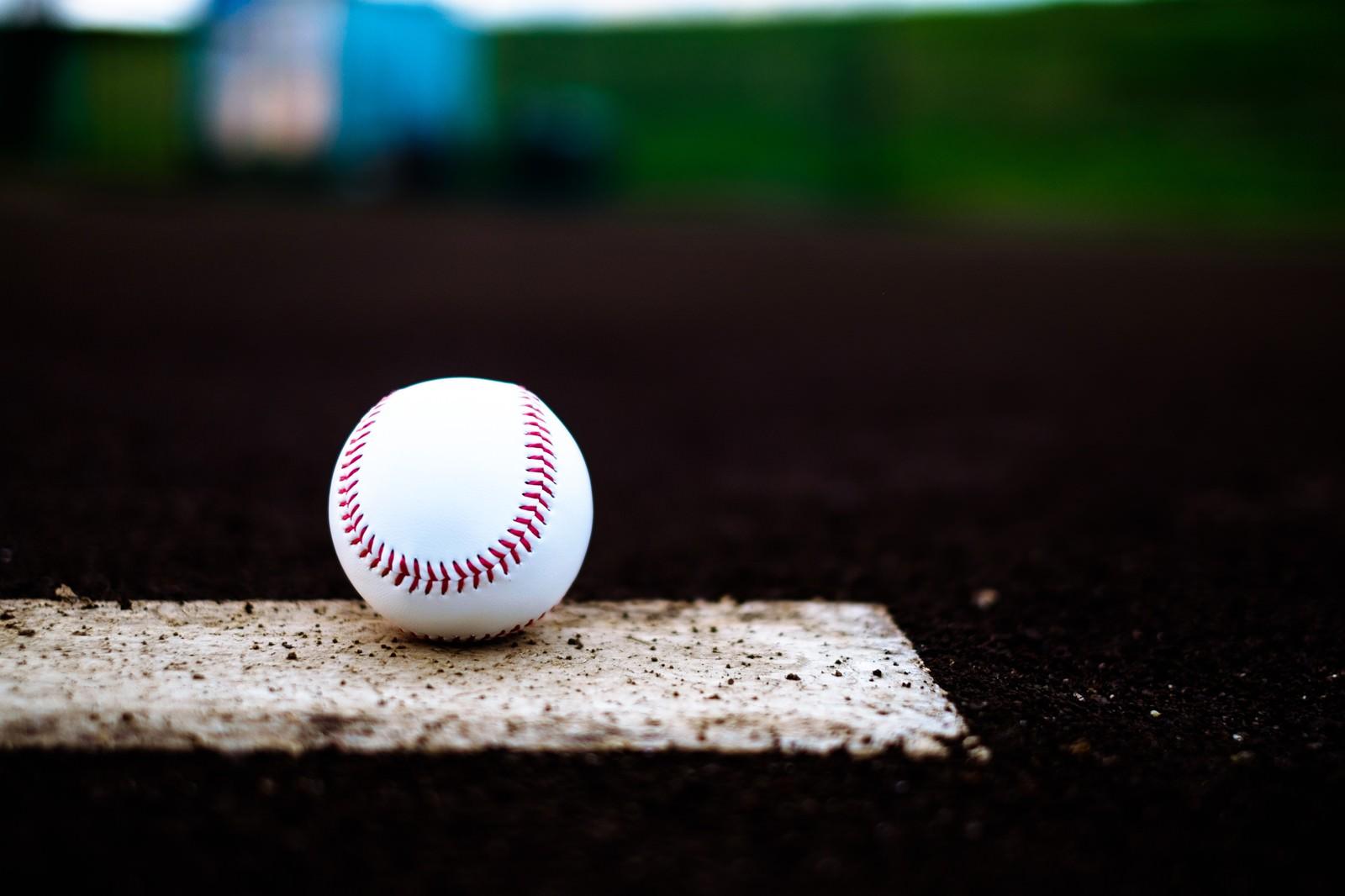 「ベース上に置かれた野球のボール」の写真