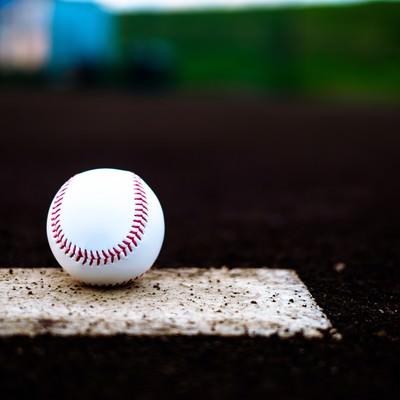 「ベース上に置かれた野球のボール」の写真素材