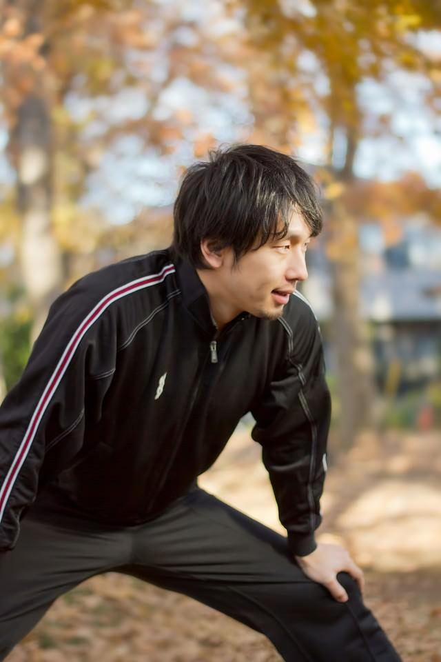 準備運動をするジャージの男性の写真