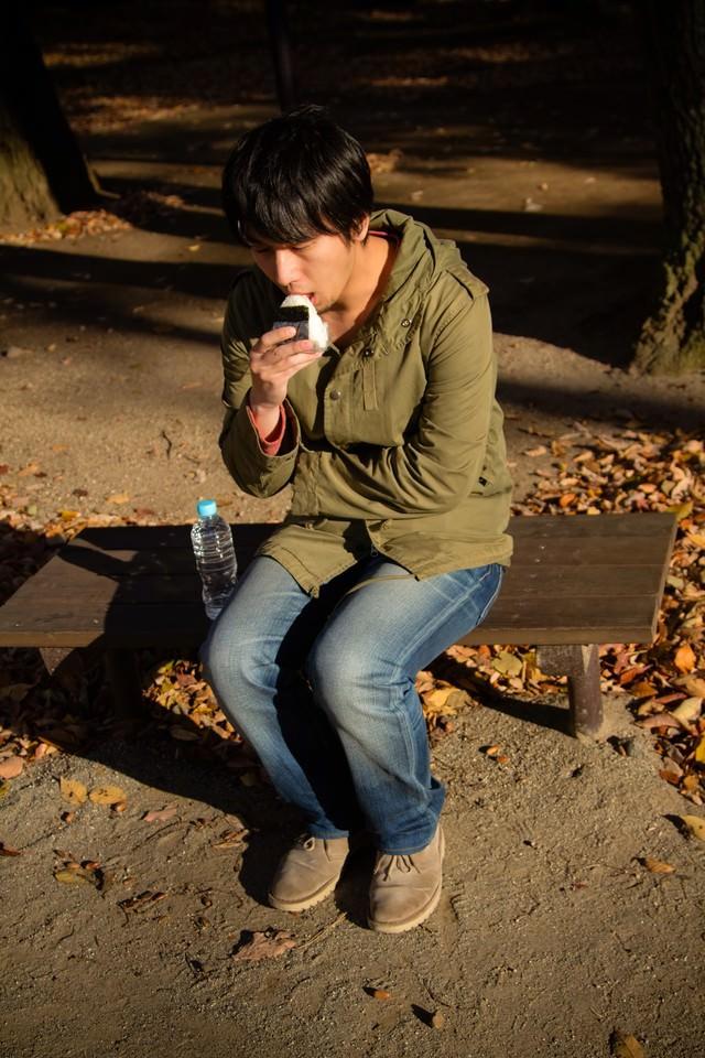 公園で寂しくおにぎりを食べる男性の写真