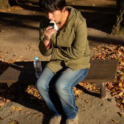 「公園で寂しくおにぎりを食べる男性」の写真素材