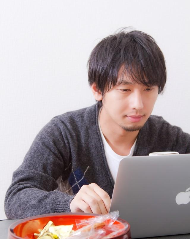 お菓子食べながらパソコンをする男性の写真