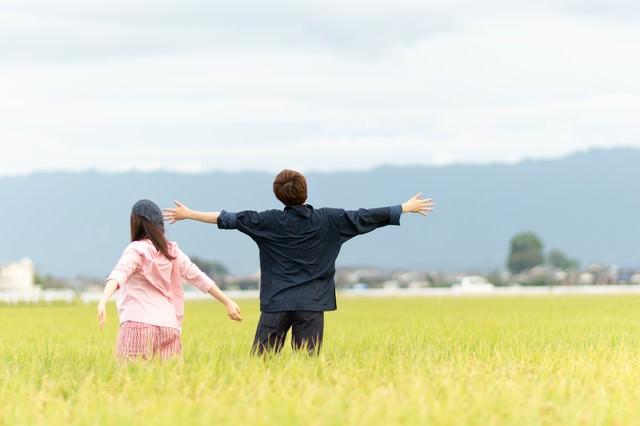 広大な田園風景に溶け込む夫婦の写真