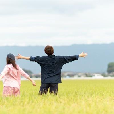 「広大な田園風景に溶け込む夫婦」の写真素材