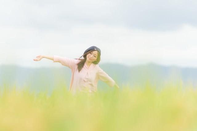 金色の稲穂ともんぺ女子の写真