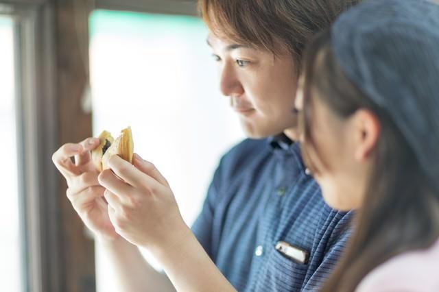 出来たての回転饅頭を食べに来た夫婦の写真