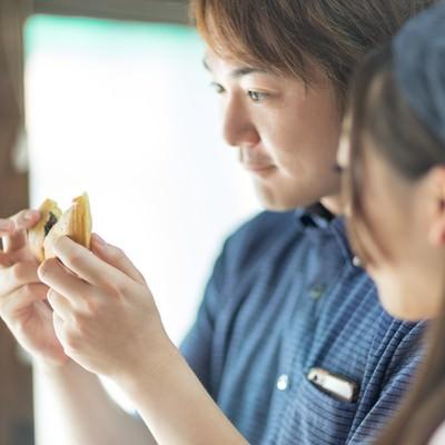 「出来たての回転饅頭を食べに来た夫婦」の写真素材