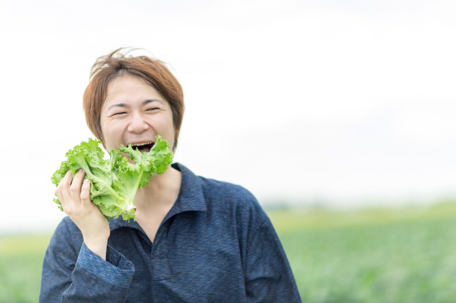 「その場で収穫したサニーレタスを頬張る農夫」の写真[モデル:五十嵐夫妻]