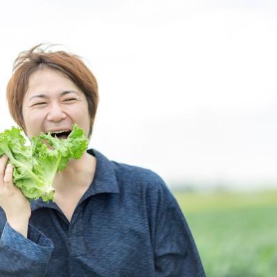 「その場で収穫したサニーレタスを頬張る農夫」の写真素材