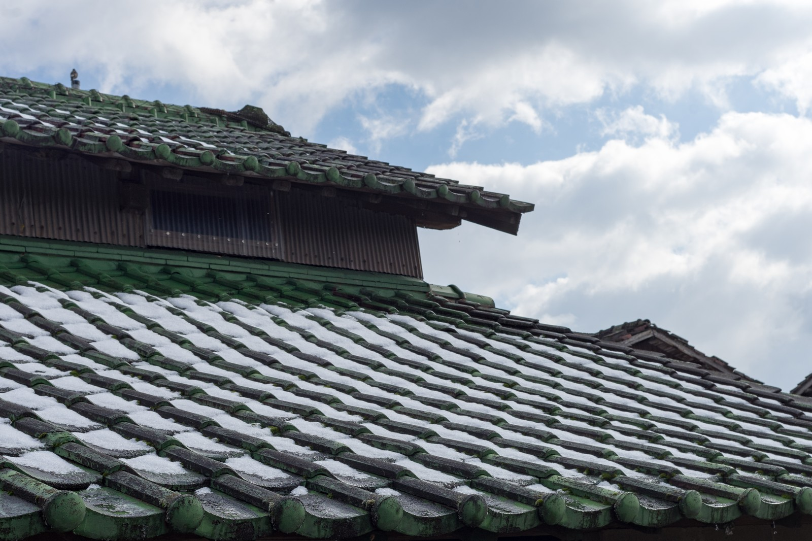 「瓦屋根に雪が残る」の写真