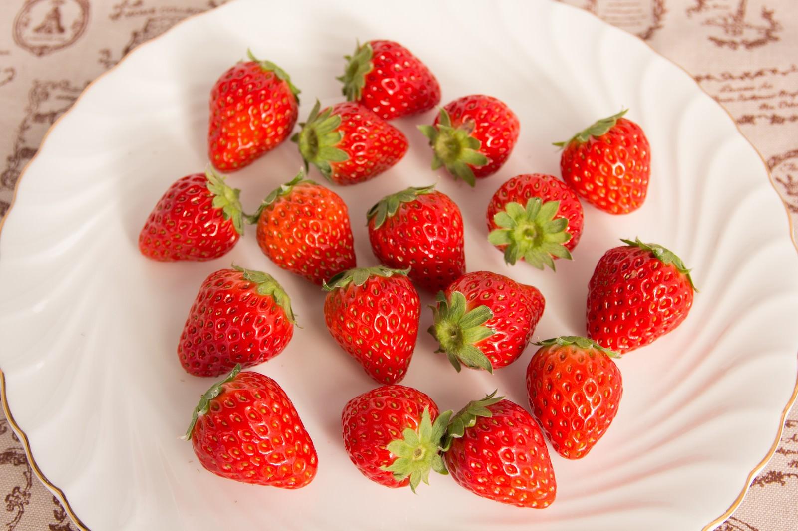 「お皿の上に散らばった採れたての苺」の写真