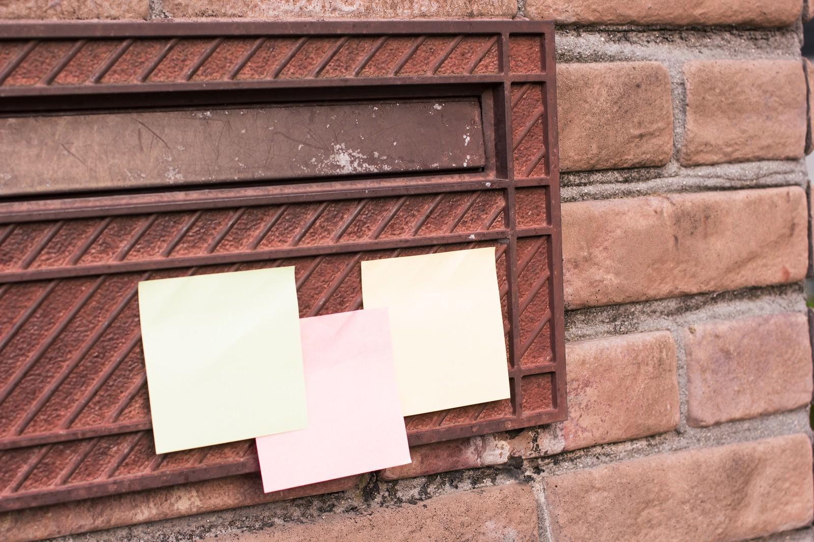 「郵便受けに貼られたメモ」の写真