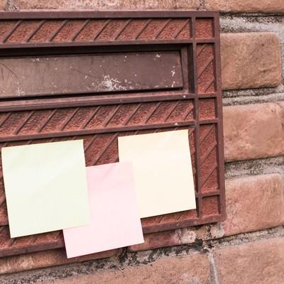 「郵便受けに貼られたメモ」の写真素材