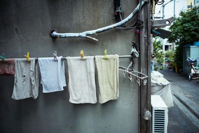 古アパートに吊るされたタオルの写真