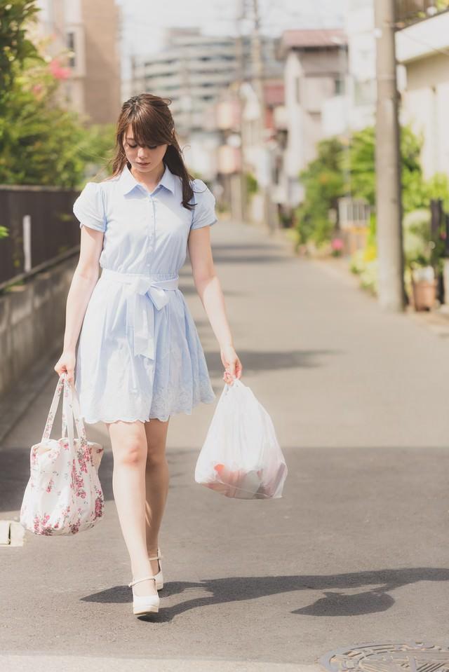 買い物袋を持って落ち込む女性の写真