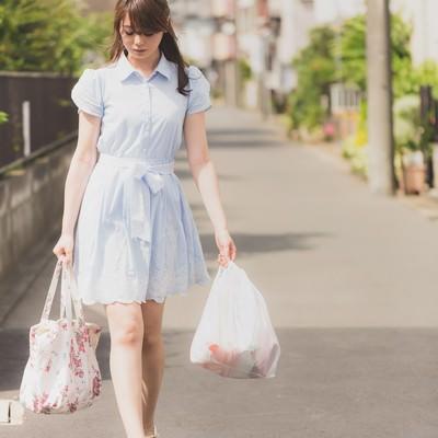 「買い物袋を持って落ち込む女性」の写真素材