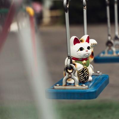 「不吉な予感!ブランコと招き猫」の写真素材