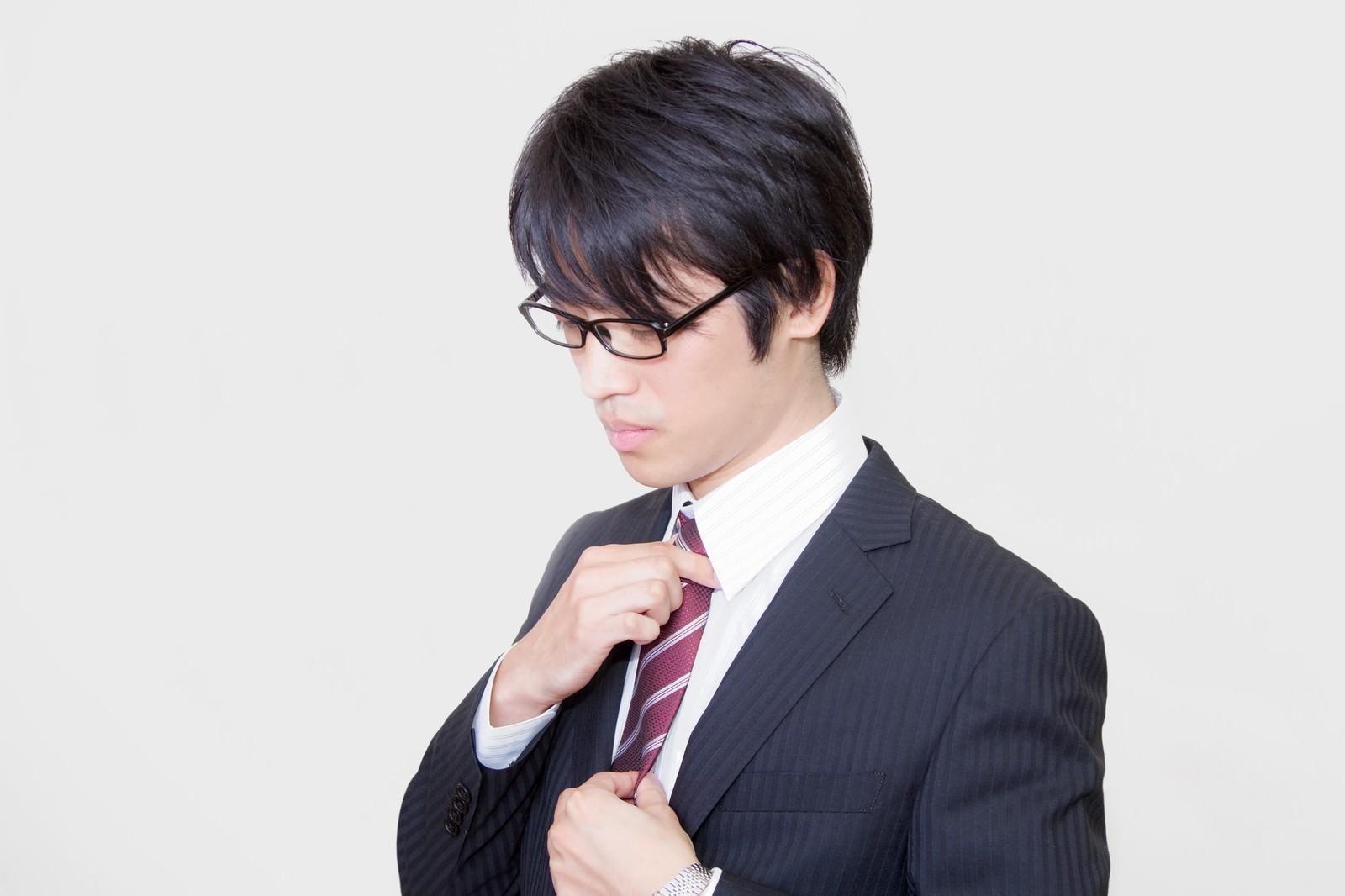 「ネクタイを直す眼鏡をかけたサラリーマン」の写真[モデル:Tsuyoshi.]