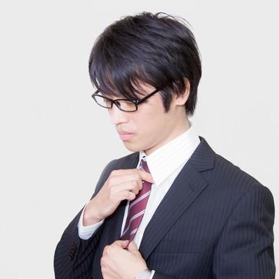 「ネクタイを直す眼鏡をかけたサラリーマン」の写真素材