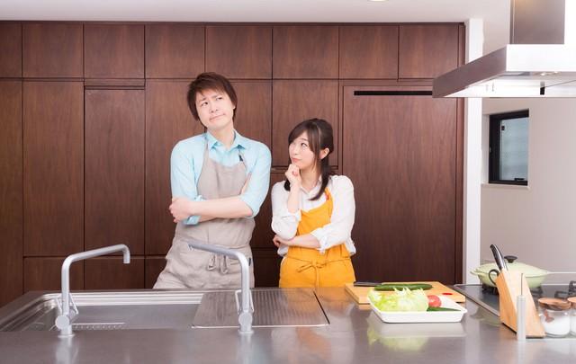 今日の夕食レシピは何にしようか?と考える夫婦の写真
