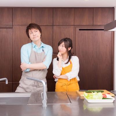 「今日の夕食レシピは何にしようか?と考える夫婦」の写真素材