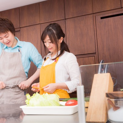 「エプロンをして料理の下準備をはじめる夫婦」の写真素材