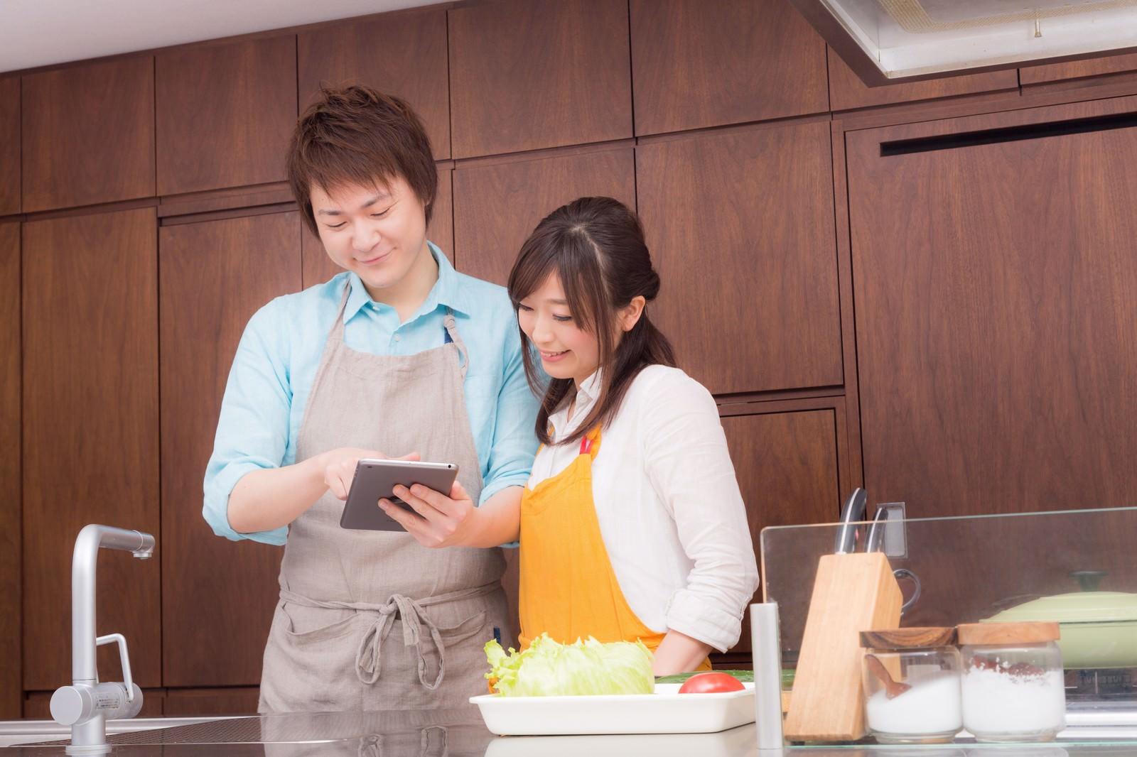 「夕飯のレシピは何を作ろうかキッチンでタブレットをみる夫婦」の写真[モデル:五十嵐夫妻]