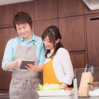「夕飯のレシピは何を作ろうかキッチンでタブレットをみる夫婦」の写真素材