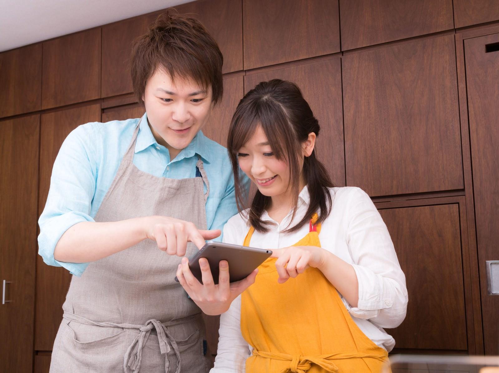 「タブレットを見ながら今日のレシピを調べる夫婦」の写真[モデル:五十嵐夫妻]