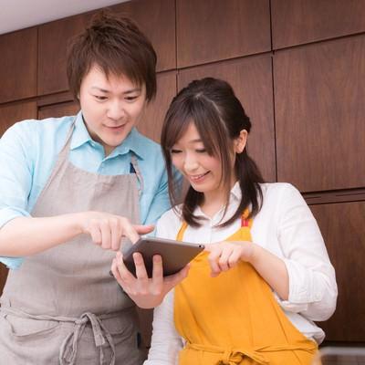 「タブレットを見ながら今日のレシピを調べる夫婦」の写真素材