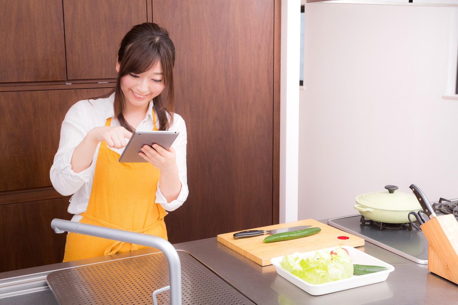 「料理をはじめる前に、タブレットでレシピを確認する嫁」の写真[モデル:五十嵐夫妻]
