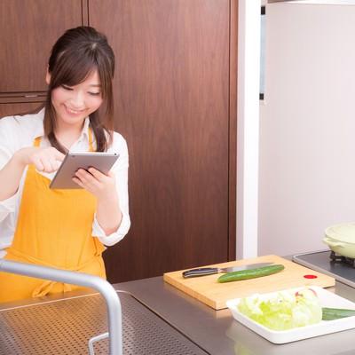 「料理をはじめる前に、タブレットでレシピを確認する嫁」の写真素材
