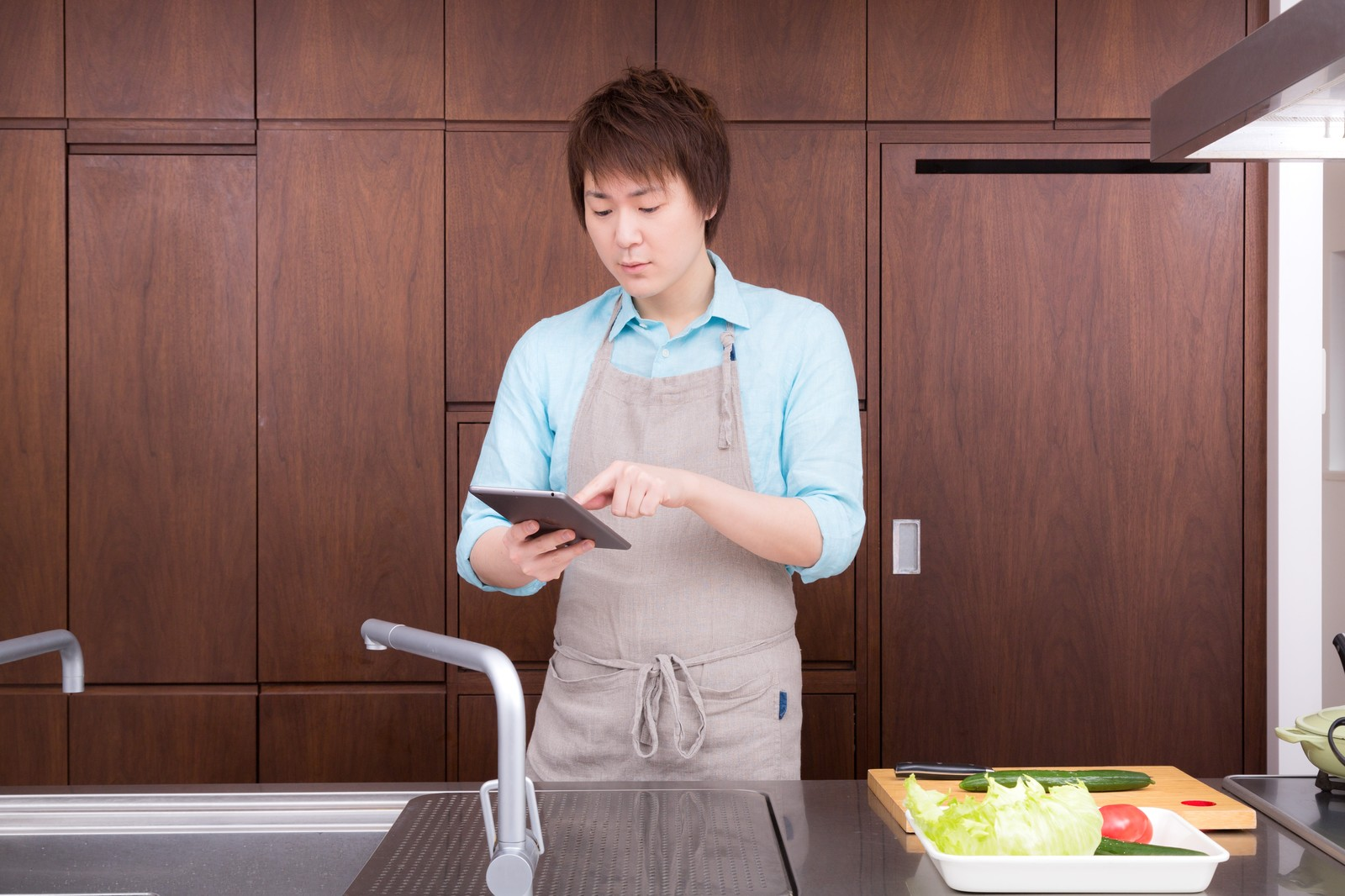 「本日の献立を確認する料理男子」の写真[モデル:五十嵐夫妻]