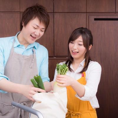 「買い物袋から野菜を取り出して料理を始める二人」の写真素材