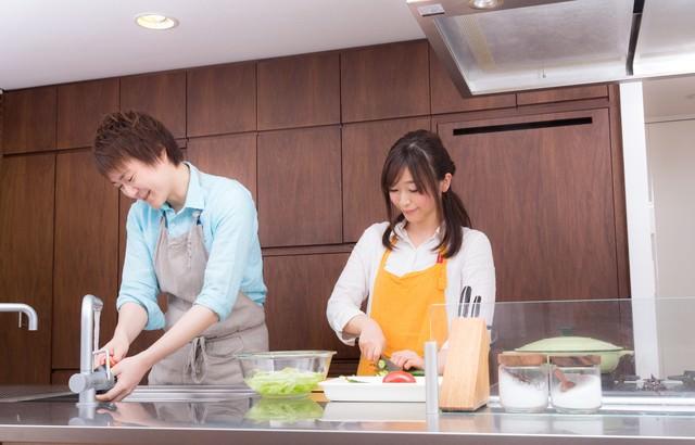 仲睦まじくキッチンで料理をする若い夫婦の写真