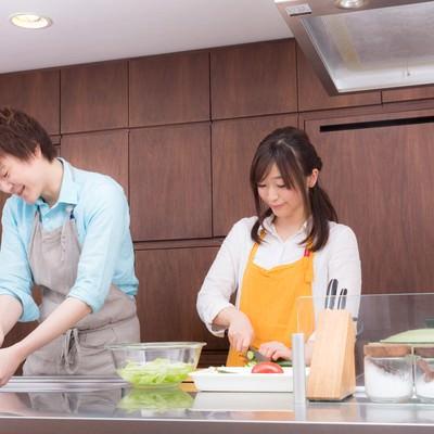 「仲睦まじくキッチンで料理をする若い夫婦」の写真素材