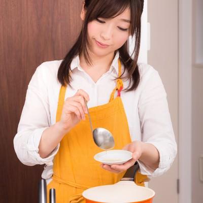 「味噌汁をつくっている妻」の写真素材