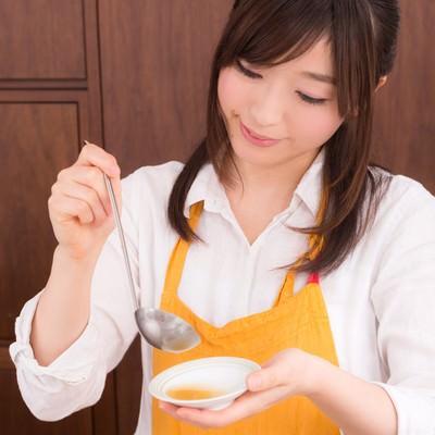 「スープの味を確かめる新妻」の写真素材