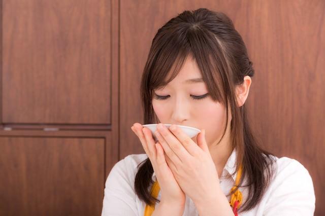お味噌汁の味見をしている若妻の写真