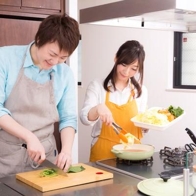 「キッチンでお鍋を一緒に作っている夫婦」の写真素材