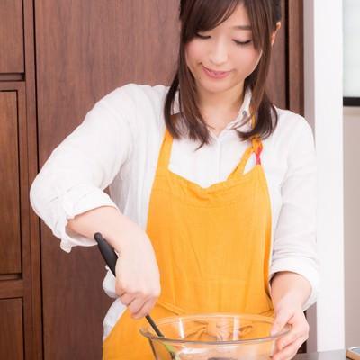 「エプロン姿で手作りチョコを作る新妻」の写真素材