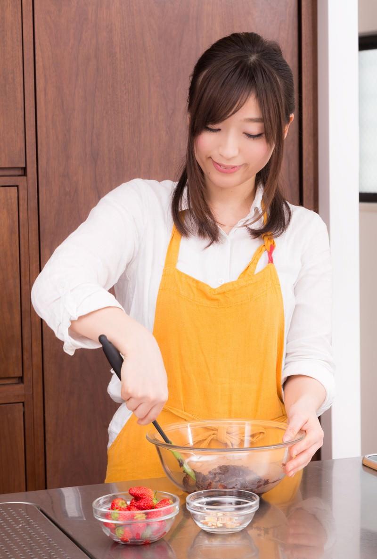 「エプロン姿で手作りチョコを作る新妻」の写真[モデル:五十嵐夫妻]