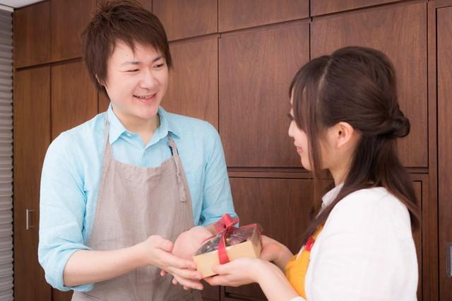 主人にバレンタインの手作りチョコレートケーキを渡す女性の写真