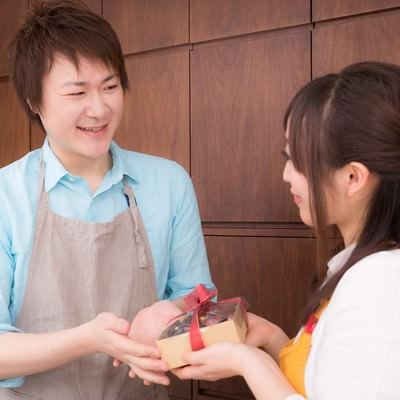 「主人にバレンタインの手作りチョコレートケーキを渡す女性」の写真素材