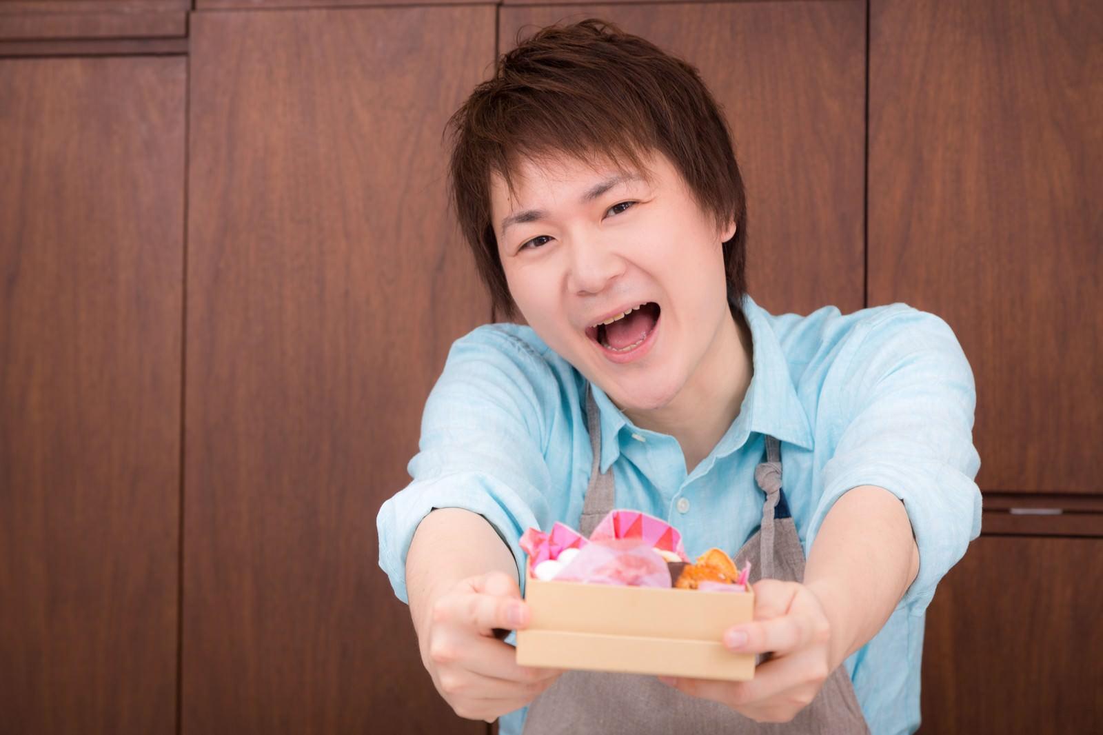 「逆チョコをプレゼントする夫」の写真[モデル:五十嵐夫妻]