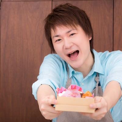 「逆チョコをプレゼントする夫」の写真素材