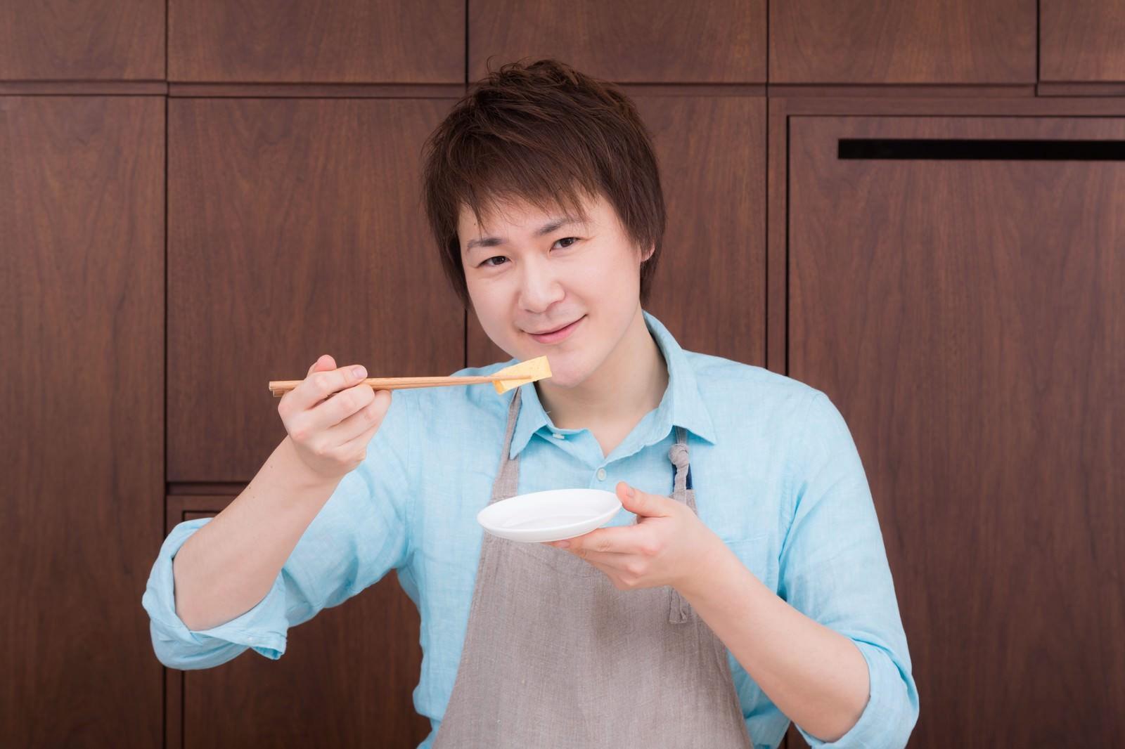 「生徒が作った玉子焼きの味を確認する料理研究家」の写真[モデル:五十嵐夫妻]
