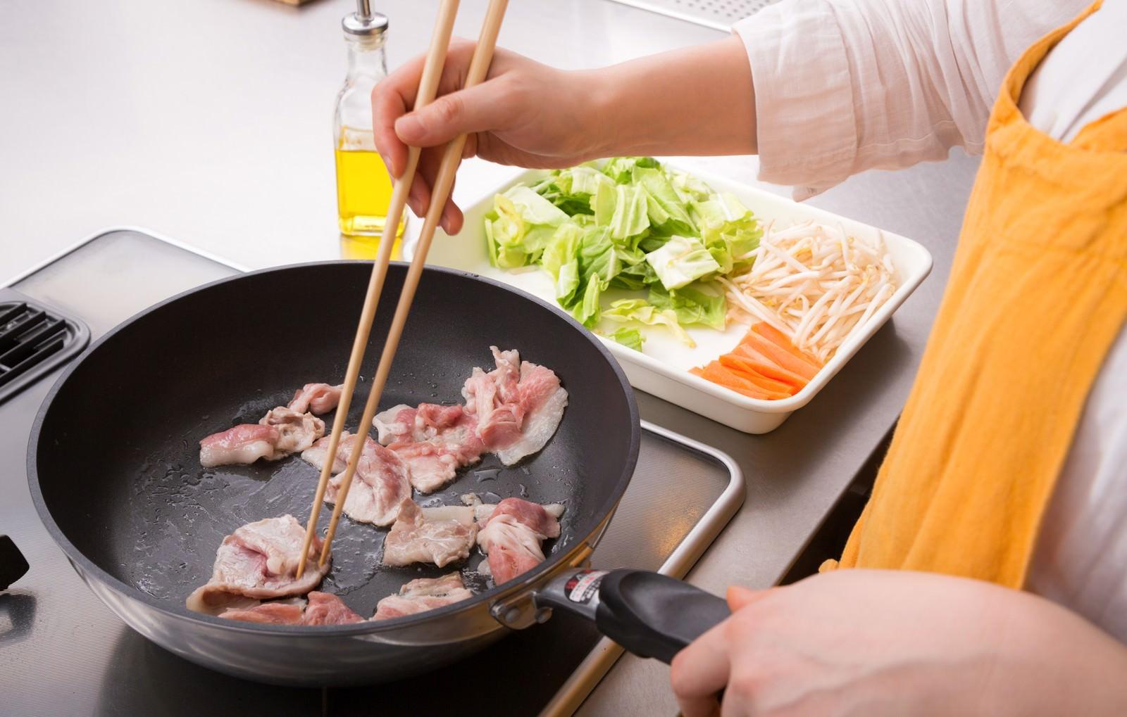 「野菜炒め、まずは豚肉をジュージュー」の写真[モデル:五十嵐夫妻]
